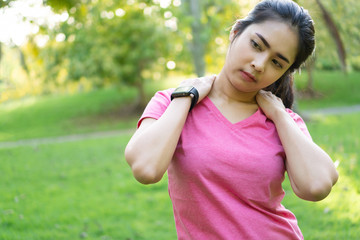 Young asian woman stretching shoulder and neck before fitness training at park.
