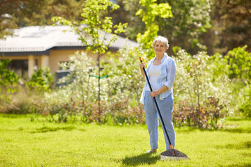 gardening and people concept - happy senior woman with lawn rake working at summer garden