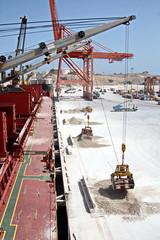 Грузовой терминал ,погрузка гипса судовыми кранами на балкер, порт Салалах, Оман, Индийский океан.