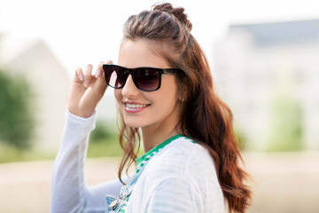 summer, eyewear and people concept - portrait of happy smiling young woman or teenage girl in sunglasses outdoors