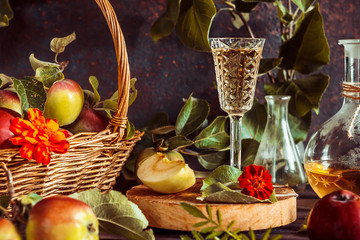 Apple cider in a glass and a decanter and basket with ripe apples on a wooden table in vintage style