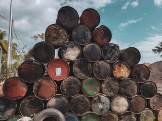 Old rusted colorful barrels from fuel or oil products over summer sky background