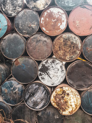Closeup of old rusted colorful barrels from fuel or oil products