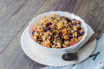 Homemade granola with oatmeal, dried fruits and nuts on a brown wooden table