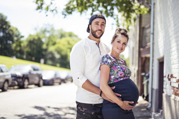 Pregnant couple portrait outside in the neighborhood