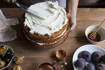 Hands spreading icing onto honey layer cake