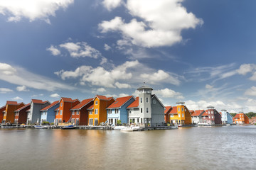 Wall Mural - colorful buildings on water over blue sky