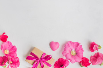 Flat lay desk with pink flowers and gift