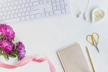 Blogger or freelancer workspace with notebook and pink flowers