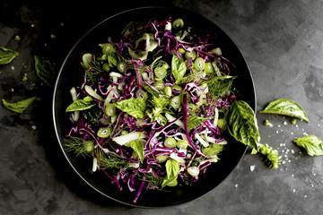 Kale Fennel Salad with Lemon Basil Pesto Vinaigrette photographed on a black background.