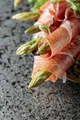 Fototapete - Asparagus wrapped in prosciutto with cress salad .