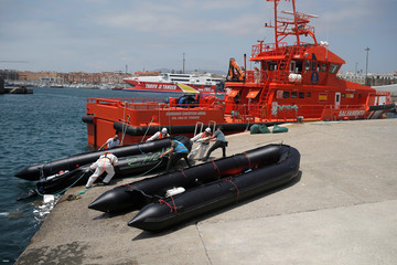 A Spanish civil guard, a member of Frontex and rescuers move a dinghy of migrants after arriving on a rescue boat at the port of Tarifa