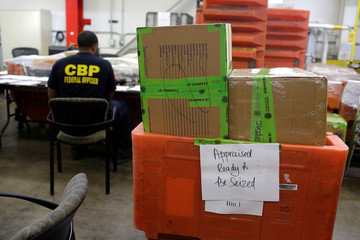 Packages already inspected by U.S. Customs and Border Protection officers sit in orange bins at the International Mail Facility at O'Hare International Airport in Chicago
