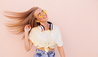 Portrait of beauty fashion smiling young women with yellow sunglasses, wireless headphones, dancing and relaxing. Flying hairs
