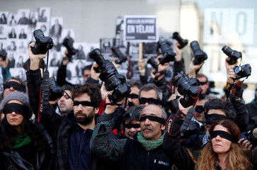 Blindfolded Argentine journalists hold up cameras during a protest against the layoff of over 300 employees from the public news agency Telam in Buenos Aires