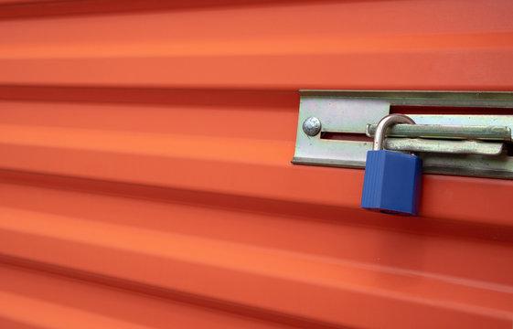 Blue plastic lock on an orange self storage unit door.