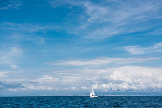 Yacht with white sails in the open sea