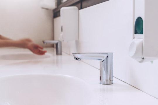 Sensor water tap in bathroom of cafe. Woman washing hands. Modern WC