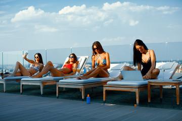Four attractive women enjoy sunbeds in penthouse