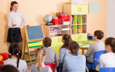 Group of pupil listening glad teacher