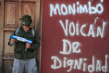 """A demonstrator poses for a photo next to a graffiti that reads """"Monimbo volcano of dignity"""" in the indigenous community of Monimbo in Masaya"""