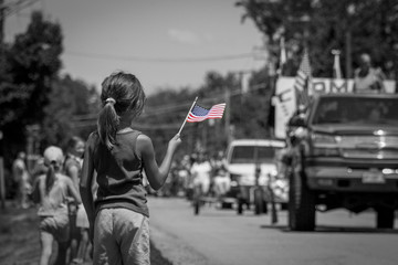 Girl waving American flag at parade in black and white Wall mural