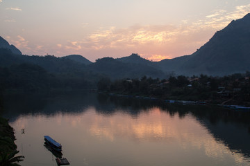 Sunset over the Pak River with a banana boat at Nong Kiaw from the guest house near Luang Prabang in Laos