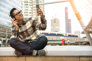 Handsome young man listen to music in smartphone and happy on holiday with easy life. time to relax on city.