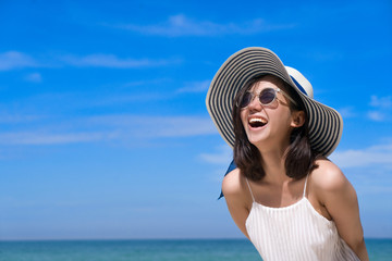 Portrait of happy smiling woman on the beach on a beautiful . Pretty girl asian in casual looking away and smile , laughing. The beach beautiful at bright sky Wall mural