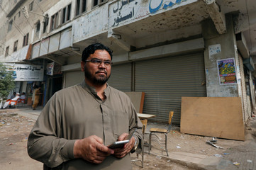 Zakir Hanif, an activist of Awami National Party, stands outside his pharmacy store which was bombed by the Tehreek-e-Taliban Pakistan, in Karachi