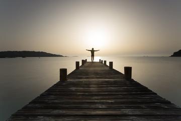 Person steht mit offenen Armen bei Sonnenaufgang am Steg