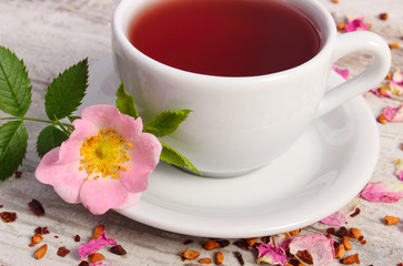 Cup of tea with wild rose flower on old rustic plank