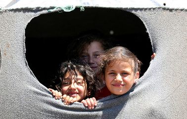 Internally displaced girls from Deraa province look out from a hole near the Israeli-occupied Golan Heights in Quneitra