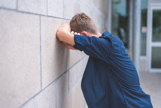 Teen crying into folded arms against a brick wall.