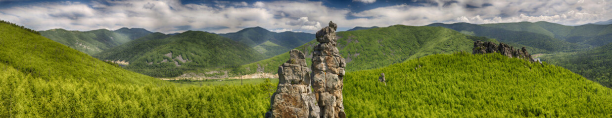 Photo sur Aluminium Colline Panoramic landscape: a large rocky peak against the background of green mountains, hills and smaller rocks, a contrasting blue sky and clouds. HDR image with polarisation lens filter