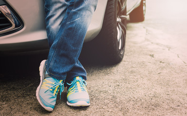 Traveller wearing jeans and sneakers standing beside the car.