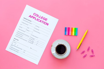 Apply college. Empty college application form near coffee cup and stationery on pink background top view copy space