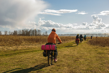 Bicyclista on rural road in spring field in Nizhny Novgorod Region, Russia