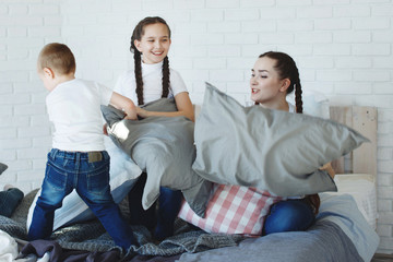 Girls with pigtails and a younger brother with pillows on the bed. The concept of a happy family.
