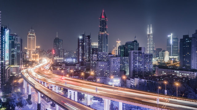 aerial view of buildings and traffic multi-level junction at night in Shanghai city