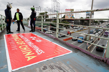 """Traffic enforcers stand next to a banner reading """"Welcome to the Philippines, Province of China"""" after removing it from an overpass along the C5 road intersection in Taguig, Metro Manila"""