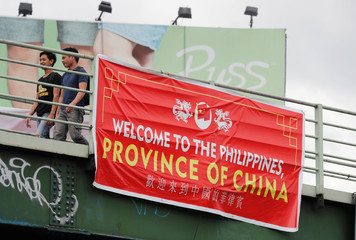 """Residents walk past a banner reading """"Welcome to the Philippines, Province of China"""" on an overpass along the C5 road intersection in Taguig, Metro Manila"""