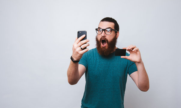 Studio shot of shocked and terrified young european man holding credit card and smartphone, standing with opened mouth from amazement over white background. Someone stole money from my account