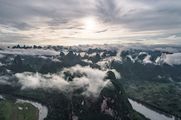 aerial view of cloudscape above farmland and mountain around the ancient town of Xingping, China