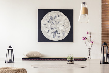 Moon poster above mat with pillow in japanese bedroom interior with lanterns and flowers. Real photo
