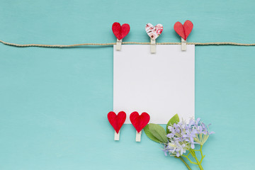White paper card with red paper heart clip and purple flower on blue background, greeting card concept, valentine card