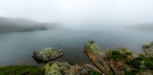 Wall Mural - idyllic mountain lake with fog lifting