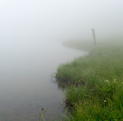 Wall Mural - mountain lake and shore in thick fog