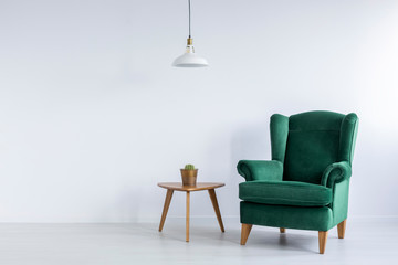 Cozy, emerald green, wing armchair and a cactus on a wooden table in a white living room interior with copy space. Real photo.