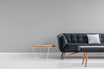 Diamond shape side table, a trendy, dark sofa and an upholstered bench in a gray living room interior with copy space. Real photo. Fotoväggar